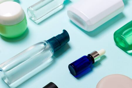 Top view of cosmetic products in different jars and bottles on blue background. Close-up of containers with copy space.
