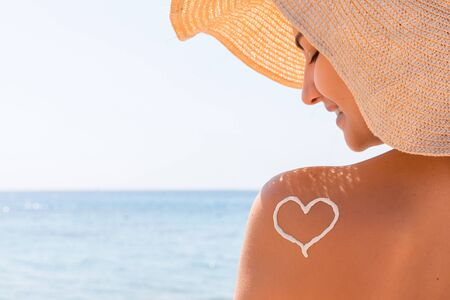 Heart made of sun cream is drawn on woman's shoulder at the beach.