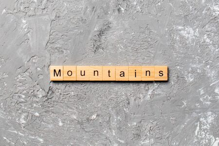 mountains word written on wood block. mountains text on cement table for your desing, concept. Banque d'images
