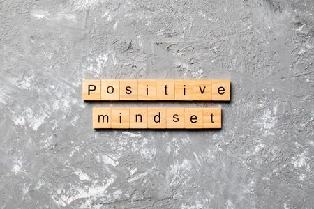 positive mindset word written on wood block. positive mindset text on cement table for your design, concept.