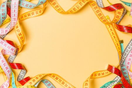 Heap of colorful measuring tapes in the form of frame on orange background. Top view of slim waist concept with copy space.