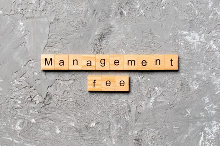 management fee word written on wood block. management fee text on cement table for your desing, concept.