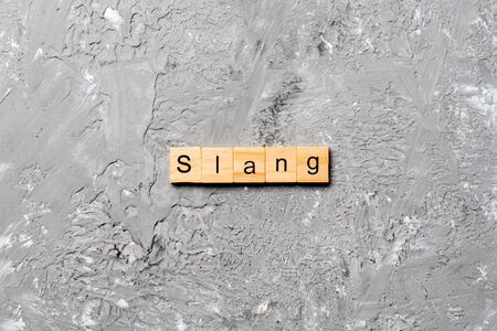 slang word written on wood block. slang text on table, concept.