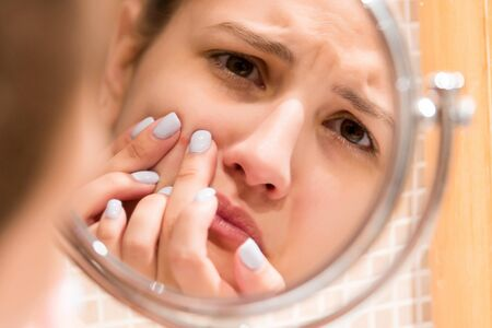 Young girl squeezes pimple on the fer face in front of a bathroom mirror. Beauty skincare and wellness morning concept. Foto de archivo