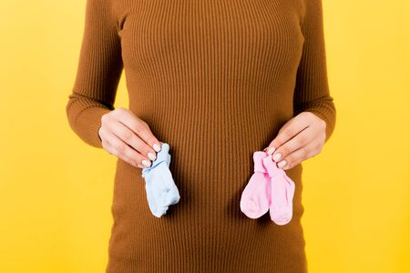 Close up of pregnant woman in brown dress holding baby pink and blue socks against her belly at yellow background. Is it a boy or a girl Child expecting concept. Expecting twins. Copy space. Foto de archivo