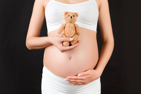 Close up of pregnant woman in white underwear holding a teddy bear against her belly at black background. Young mother is expecting a baby. Copy space.
