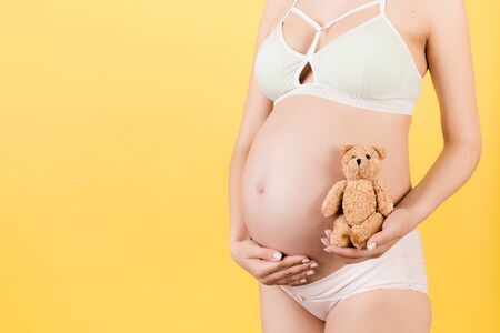 Cropped image of teddy bear in hand against pregnant woman's belly in colorful underwear at yellow background. Waiting for a childbirth. Copy space.