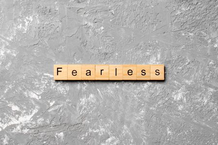 Fearless word written on wood block. Fearless text on cement table for your desing, concept.