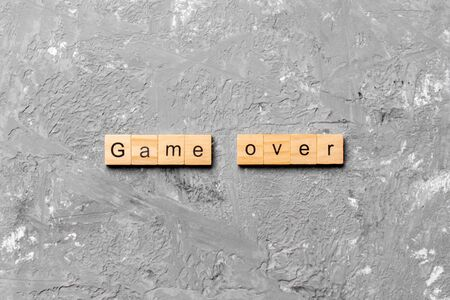 game over word written on wood block. game over text on table, concept.