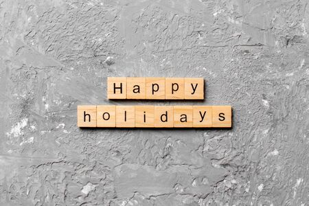 Happy Holidays word written on wood block. Happy Holidays text on cement table for your desing, concept.