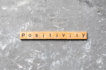 positivity word written on wood block. positivity text on cement table for your desing, concept.