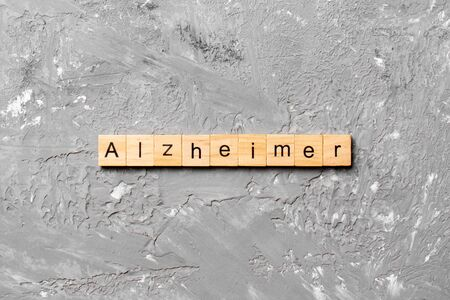 Alzheimer word written on wood block. Alzheimer text on cement table for your desing, concept. Stok Fotoğraf