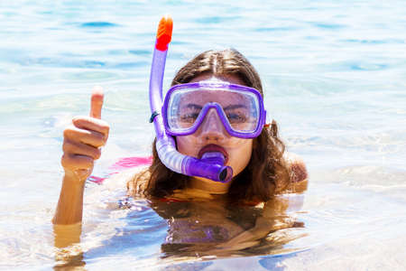 Young woman is wearing diving mask and swimming tube in the sea. Snorkeling equipment. Archivio Fotografico
