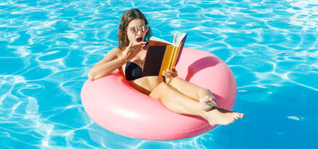Young woman is reading a book sitting on the inflatable ring in the swimming pool. Summer relaxation concept .