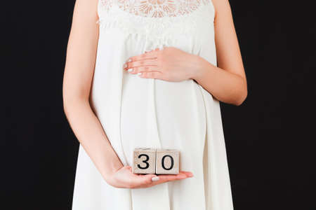 Cropped image of pregnant woman in white dress showing thirty weeks of pregnancy cubes at black background. Waiting for a baby. Copy space.