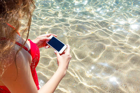 Young girl in a red swimsuit is taking a photo of the sea with her mobile phone on her vacation. Beach concept.