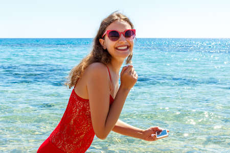 Surprised girl in a red swimsuit is taking a photo with her phone in the sea. Beach concept. Archivio Fotografico