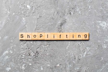 Shoplifting word written on wood block. Shoplifting text on cement table for your desing, Top view concept. Archivio Fotografico