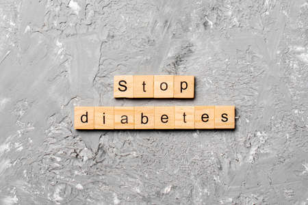 Stop diabetes word written on wood block. Stop diabetes text on cement table for your desing, Top view concept.