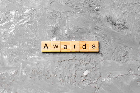 AWARDS word written on wood block. AWARDS text on cement table for your desing, concept. Archivio Fotografico