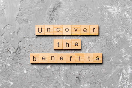 uncover the benefits word written on wood block. uncover the benefits text on table, concept. Archivio Fotografico