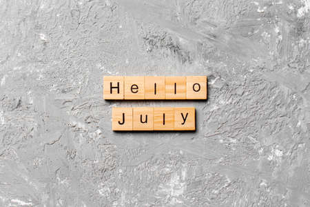 hello july word written on wood block. hello july text on table, concept.