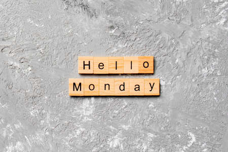 hello monday word written on wood block. hello monday text on cement table for your desing, concept. Stock Photo
