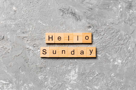 hello sunday word written on wood block. hello sunday text on cement table for your desing, concept. Archivio Fotografico