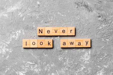 Never look away word written on wood block. Never look away text on cement table for your desing, concept.