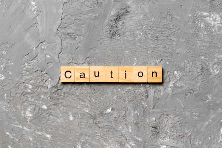 CAUTION word written on wood block. CAUTION text on cement table for your desing, concept.