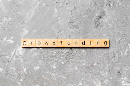 CROWDFUNDING word written on wood block. CROWDFUNDING text on cement table for your desing, concept.