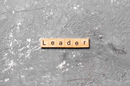 leader word written on wood block. leader text on cement table for your desing, concept.