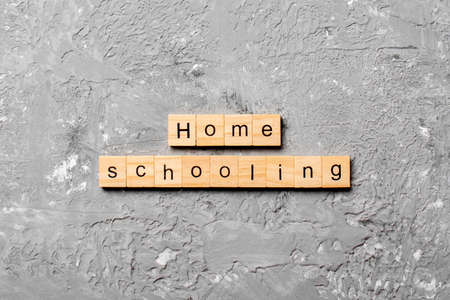Home schooling word written on wood block. Home schooling text on table, concept.