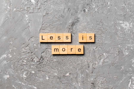 less is more word written on wood block. less is more text on table, concept.