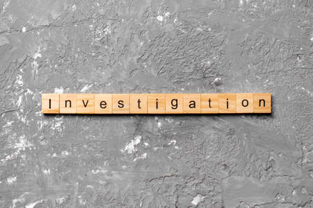 investigation word written on wood block. investigation text on table, concept.