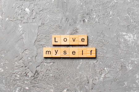 Love myself word written on wood block. Love myself text on cement table for your desing, Top view concept.