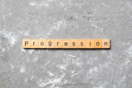 progression word written on wood block. progression text on cement table for your desing, concept.