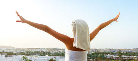 Back view of pretty girl on a balcony wrapped in white towel after having a bath. Woman is enjoying a mountain view and the sunset. Spa concept. 版權商用圖片
