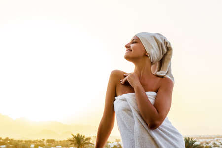 Front view of young woman standing on a balcony wrapped in white towel after having a shower. Girl is enjoying a mountain view and the sunset. Clean and fresh concept.