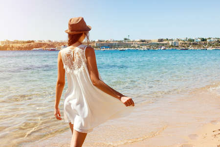 Beautiful girl is walking by the sea on a summer sunny day. Time for vacation.