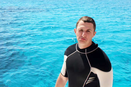 Portrait of happy scuba diver. Man is preparing for his diving lesson in the blue sea.