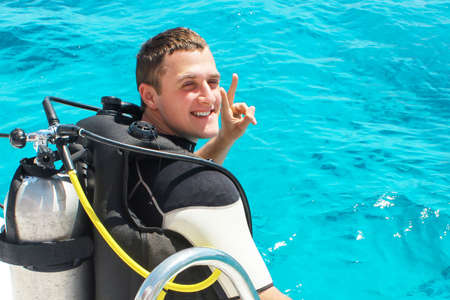 Scuba diver is preparing for diving into blue water from the boat. Underwater equipment.