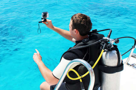 Happy scuba diver with equipment and camera is preparing for his diving lesson in the blue sea.