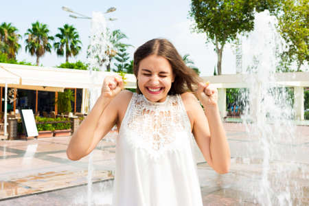 Portrait of cheerful girl in a white dress enjoying the spray of fountain on a summer day