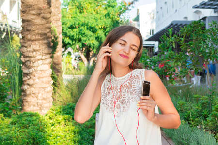 Happy smiling young pretty woman is listening to music in headphone and having fun.