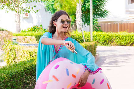 Beautiful girl is going to the beach with an inflatable circle listening to music on phone and having fun Reklamní fotografie