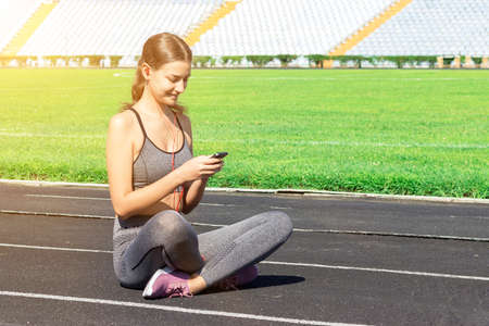 Young fit woman is sitting on a jog track and listening to music on headphones at the stadium. Athlete is relaxing after active training.