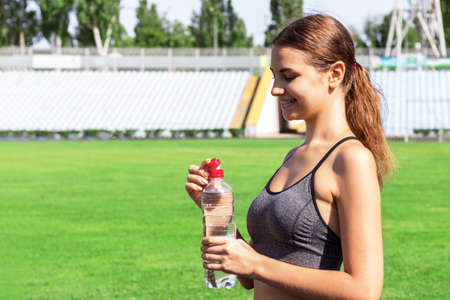 Beautiful woman is drinking water and listening to the music on headphones at the stadium. Girl is having a break after training. Reklamní fotografie