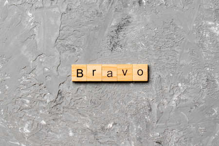 BRAVO word written on wood block. BRAVO text on cement table for your desing, concept.