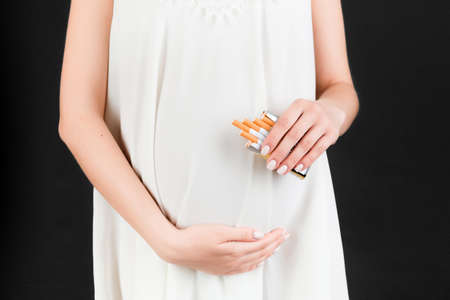 Cropped image of a pack of cigarettes in pregnant woman's hands at black background. Risk of abortion. Smoking addiction. Dangerous habit.